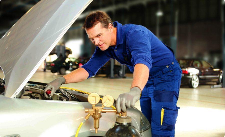 Monteur voert een aircoservice uit aan een auto bij Premio Van Essen met behulp van een aircoapparaat