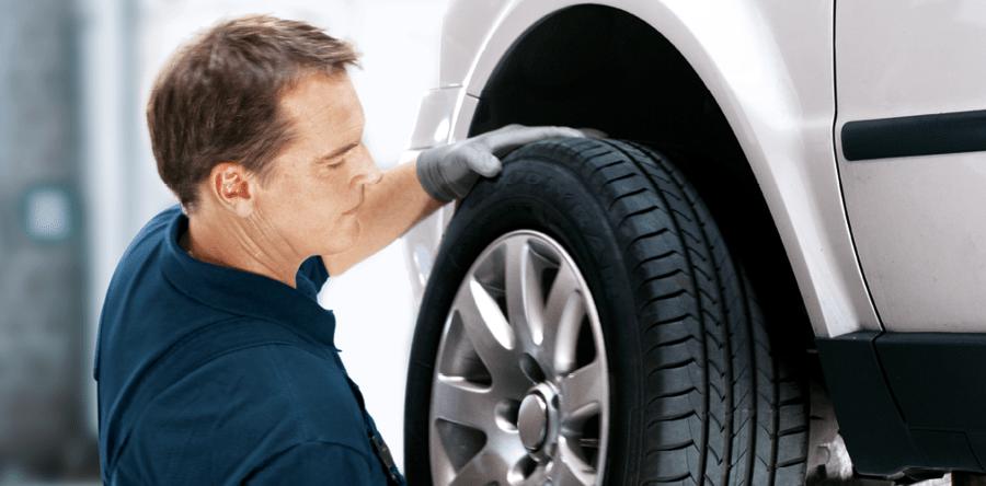 Een monteur wisselt een wiel met band aan een auto