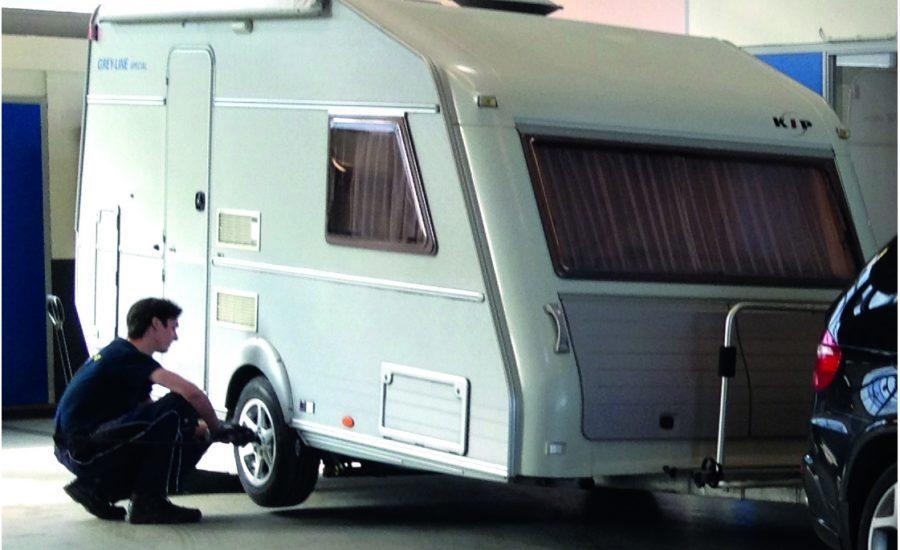 Een automonteur van Premio Van Essen vervangt de banden van een caravan