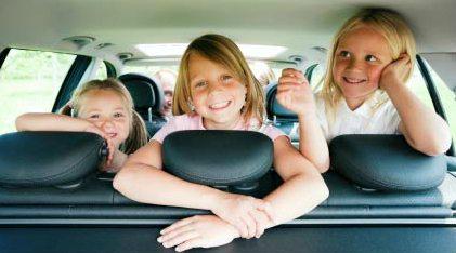 Meisjes op de achterbank in een auto met airco