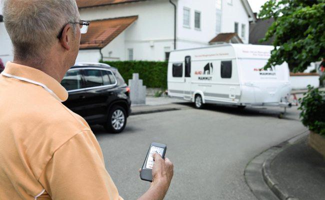 Een man zet met behulp van een mover de caravan (zonder duwen en trekken) op de oprit