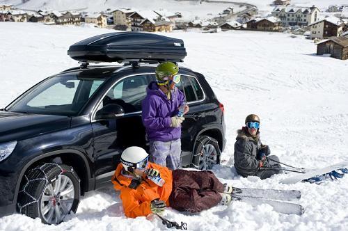 Skiers rusten uit voor een auto met sneeuwkettingen