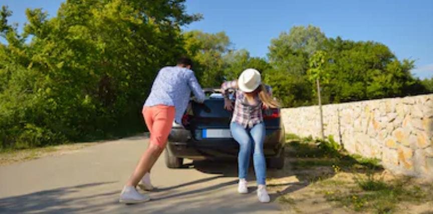 Een jonge man en vrouw duwen een auto tijdens vakantiereis een heuvel op