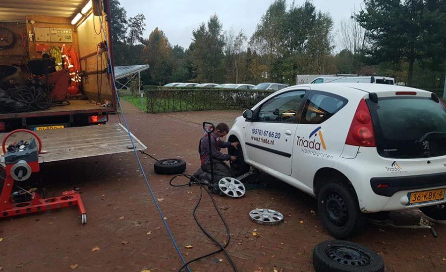 Zomer en winterbanden wissel op locatie bij triada van een auto