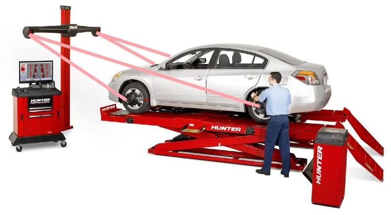 Auto op uitlijnbrug en een persoon is auto aan het uitlijnen