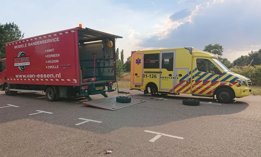 Een band van een ambulance wordt vervangen op een parkeerplaats langs de weg