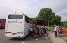 Van Essen voert een 24 uurs bandenpechservice aan een bus uit terwijl de schoolkinderen erom heen staan te kijken