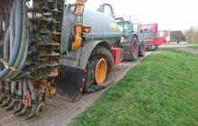 pechservice door Van Essen van een grote kapotte giertank op dijk langs de IJssel