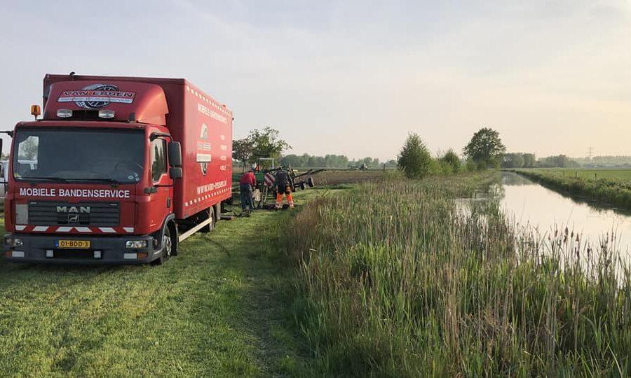 Een pechservice van een hooischudder in land langs het water