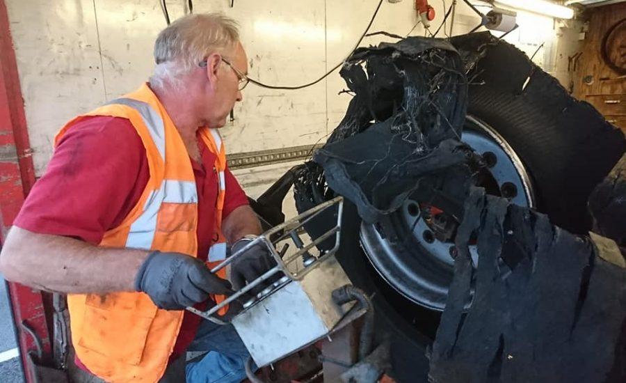 Een monteur demonteert een volledig uit elkaar geklapte truckband van de velg in de mobiele servicetruck