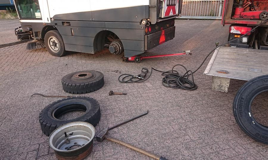 Een compleet wiel en een gedemonteerde band/wiel combinatie van een veegmachine liggen op de grond