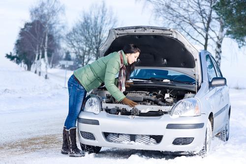 Vrouw kijkt onder motorkap van auto in besneeuwd landschap